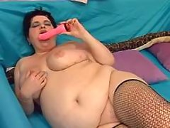 Horny fatty dildoes herself on sofa