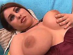 Chesty redhead masturbates on sofa